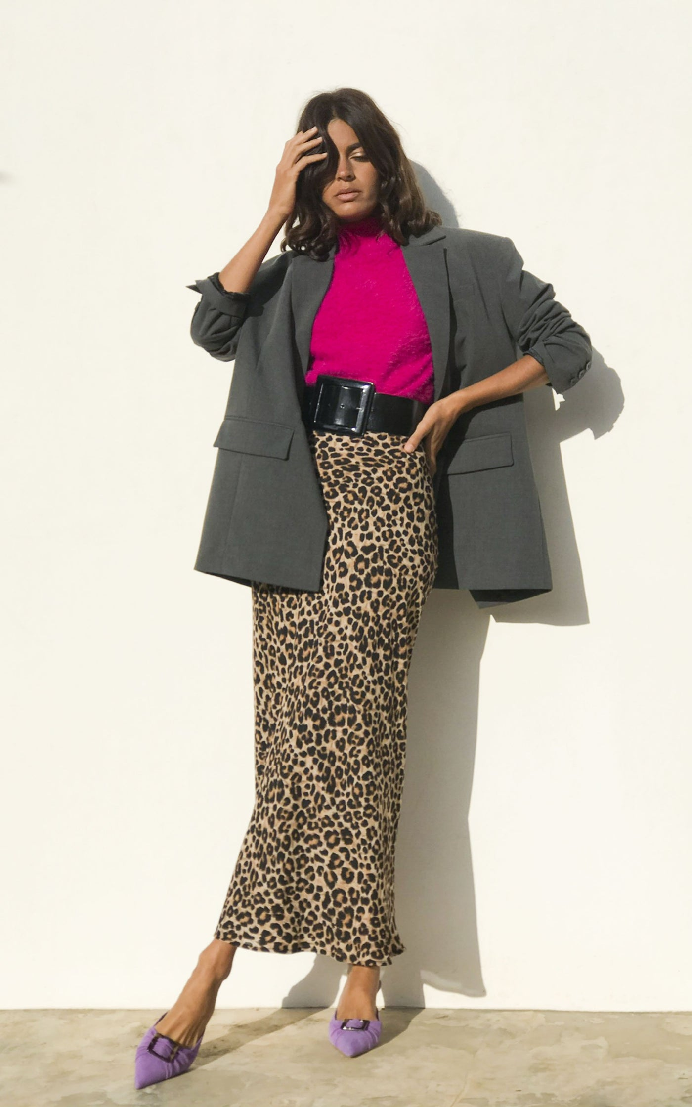 Model wears  Dancing Leopard sophie skirt in rich leopard with bright pink jumper and lilac shoes facing forwards with an oversized grey blazer