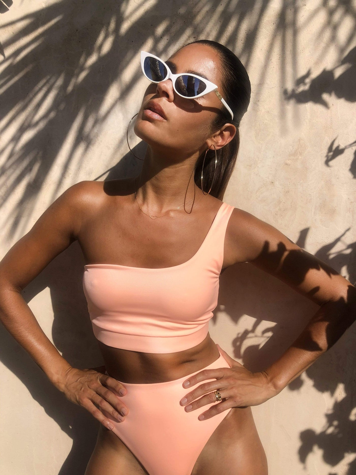 Dancing Leopard side facing model poses with hands on hips wearing Calypso Bikini Bottom In Peach styled with white sunglasses