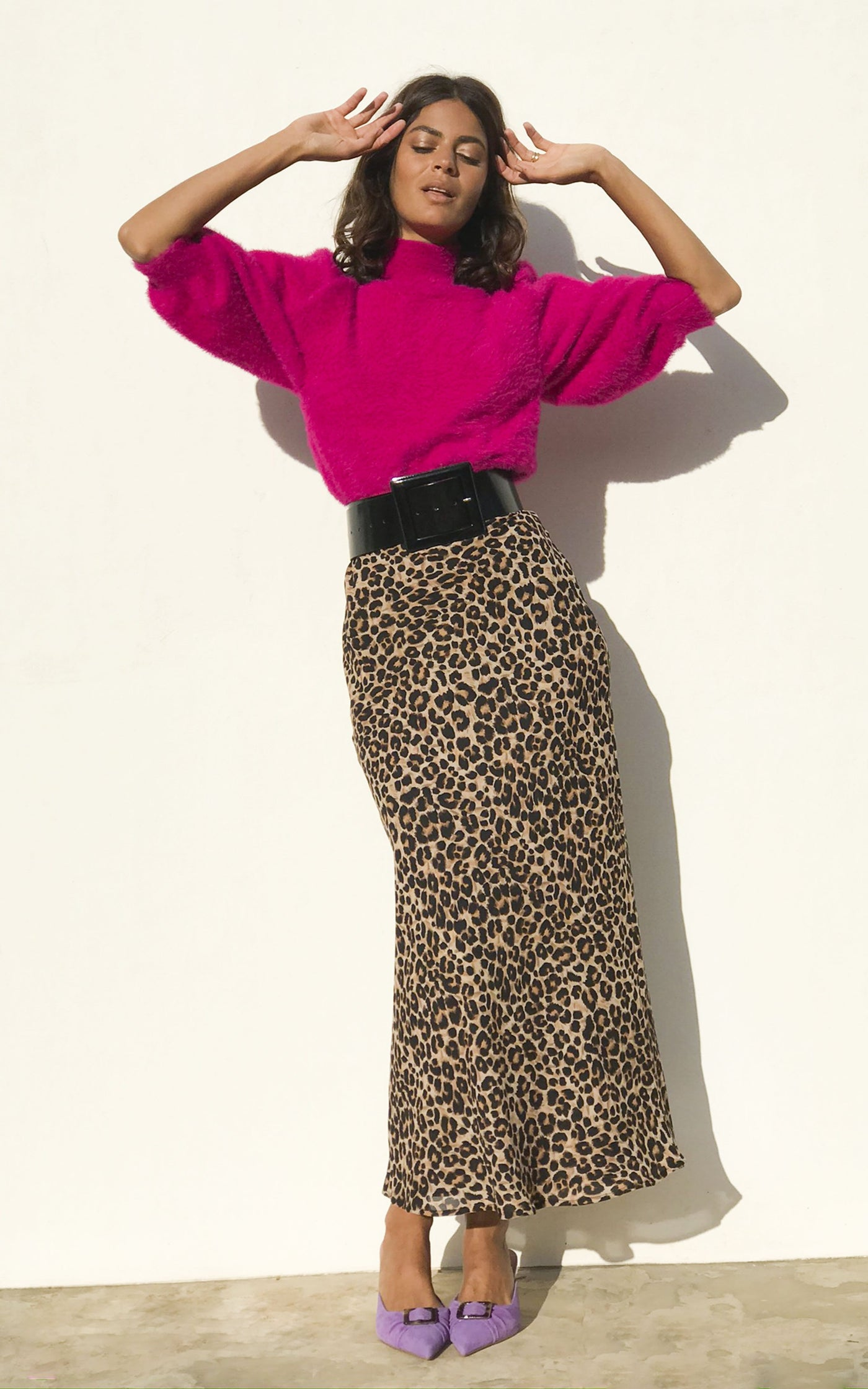 Model wears Dancing Leopard sophie skirt in rich leopard with bright pink jumper and lilac shoes facing forward with hands above her head