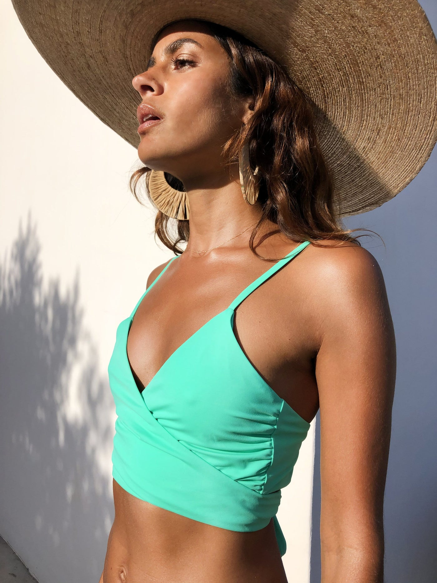 Sideways close up of Dancing Leopard model wearing Oyster Bikini Top in aqua with straw hat and earrings