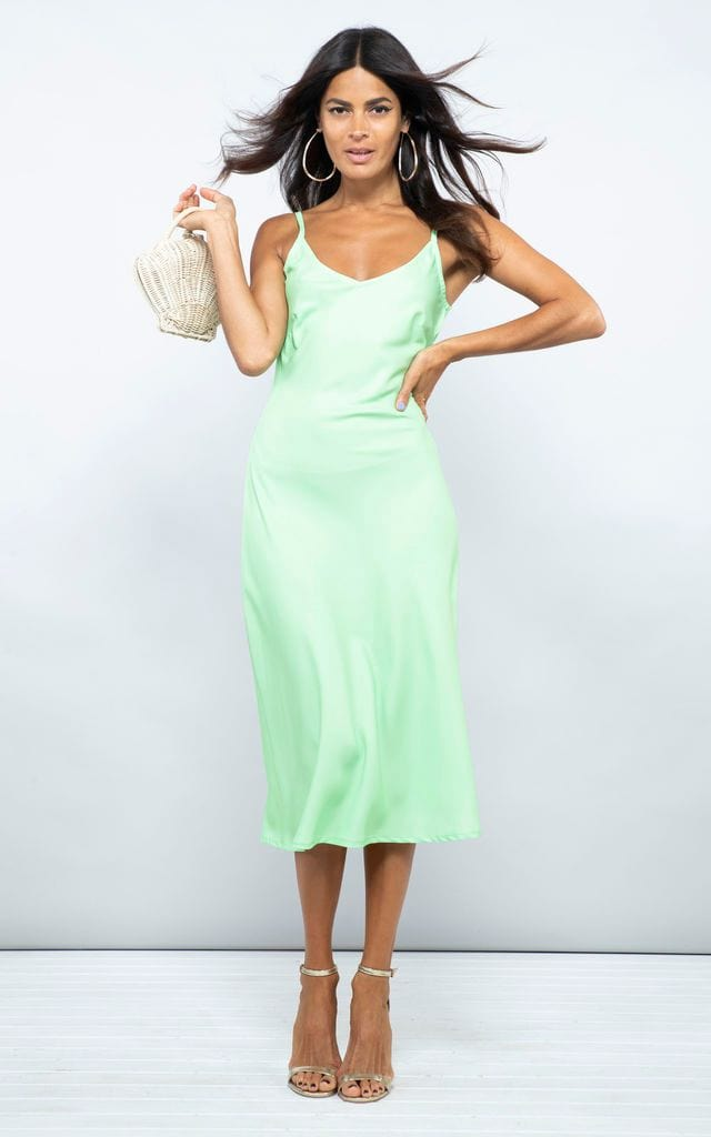 Dancing Leopard model faces forward holding bag wearing Jade Midi Dress in lime green