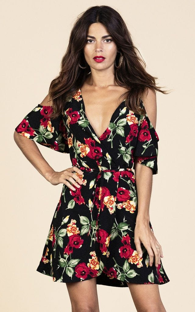 Dancing Leopard model faces forward with hand on hip wearing Marlin Dress in wild rose print