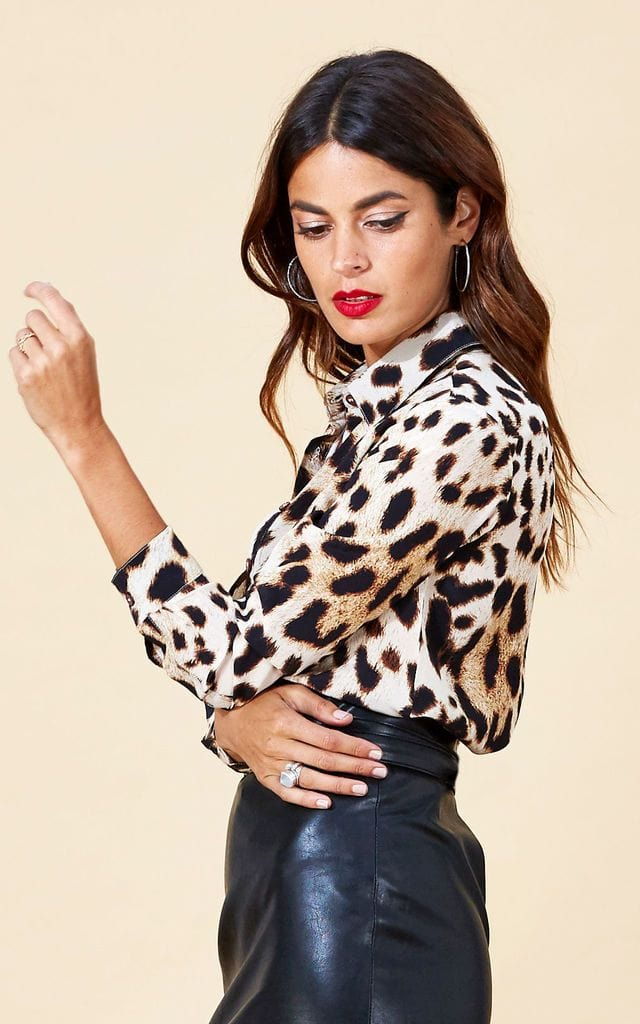 Model faces sideways with arm up wearing San Diego Shirt in leopard print with black skirt