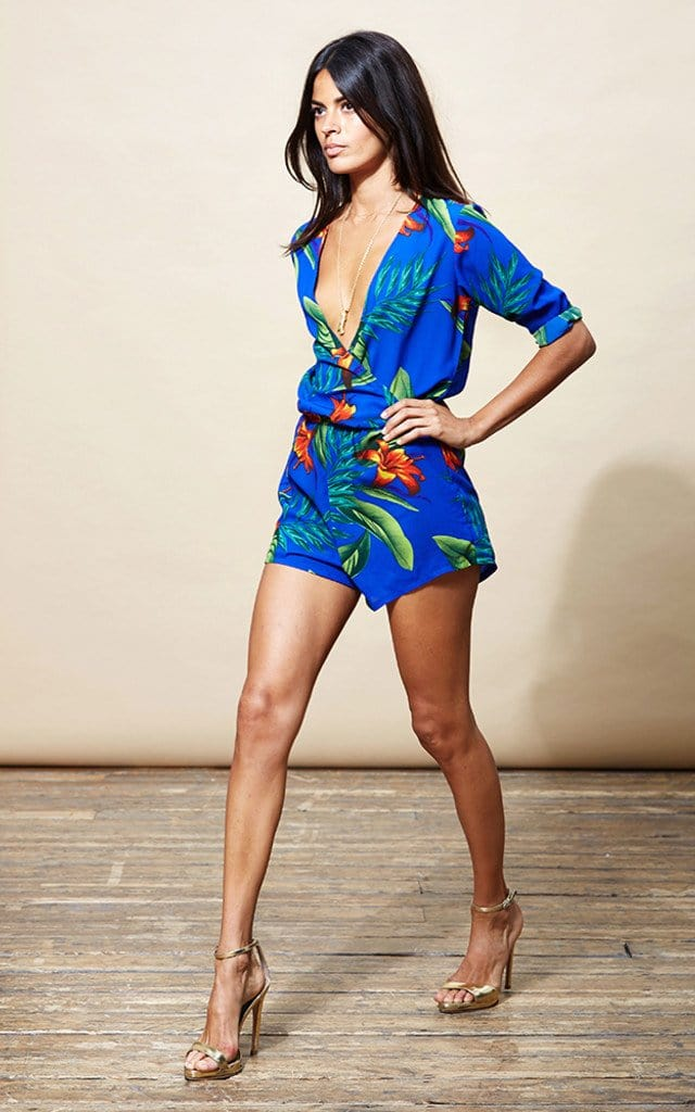 Dancing Leopard model walks forward with hands on hips wearing Tiago Playsuit in blue tropical print