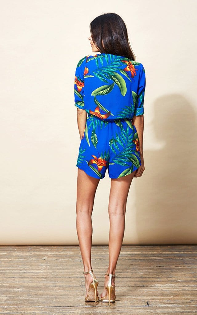 Model faces backwards wearing Dancing Leopard Tiago Playsuit in blue tropical print with heels