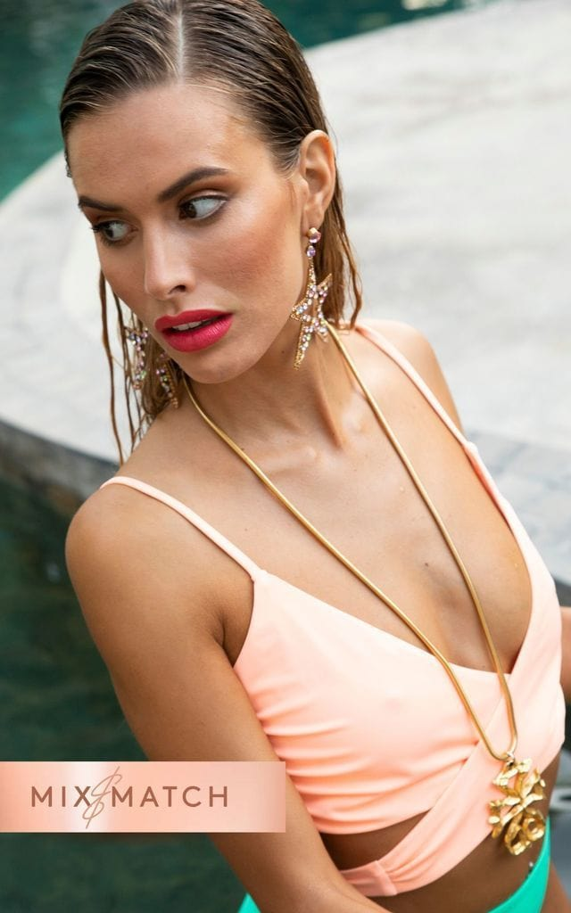 Dancing Leopard model looks over shoulder wearing Oyster Bikini Top in peach with star earrings