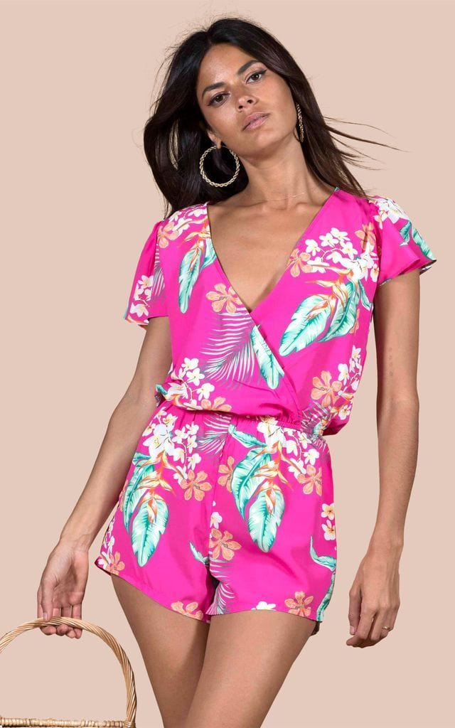 Brunette model faces forwards holding bag wearing Rio Playsuit in cerise tropical print