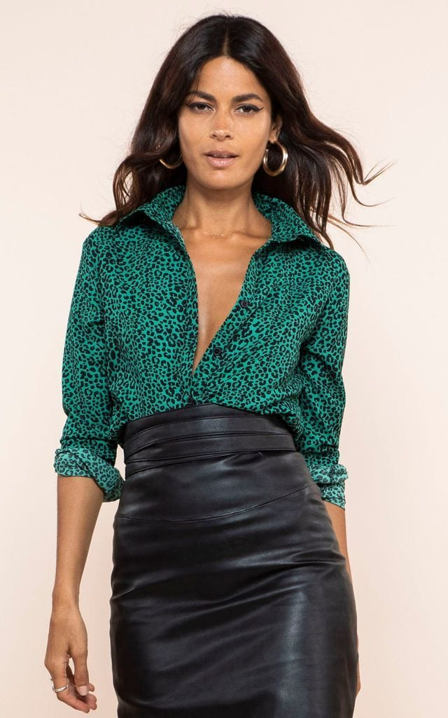 Dancing Leopard model walks forward wearing San Diego Shirt in green leopard print with PU skirt