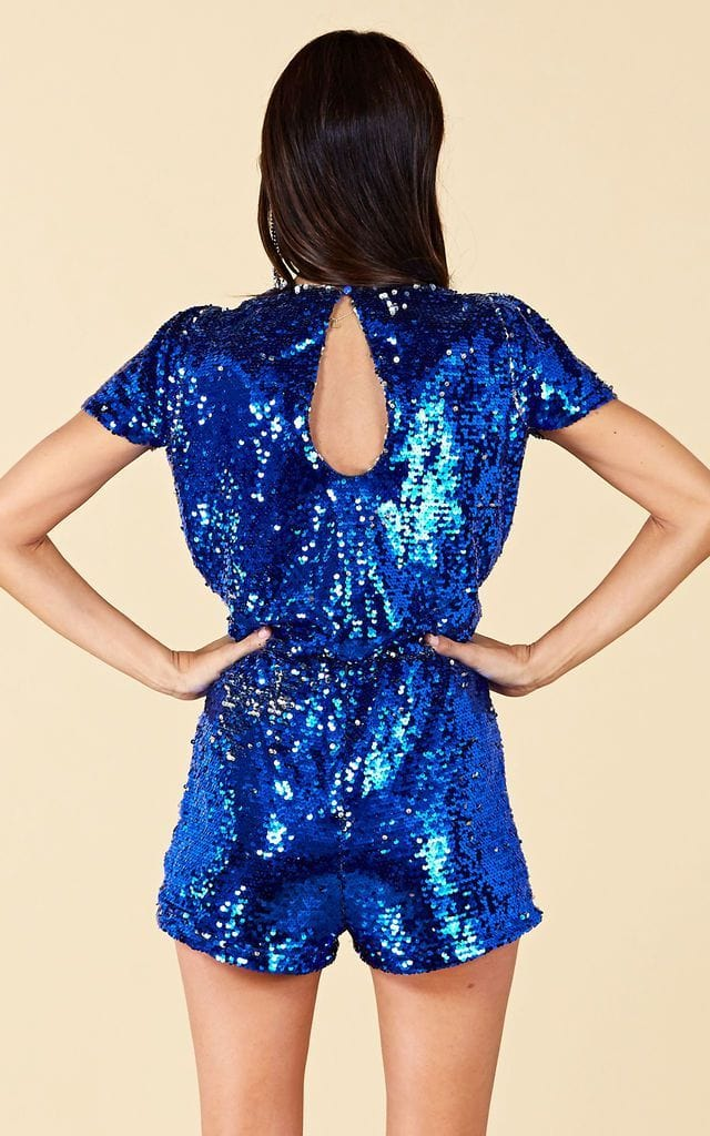 Model faces backwards with hands on hips wearing Supernova Sequin Playsuit in blue