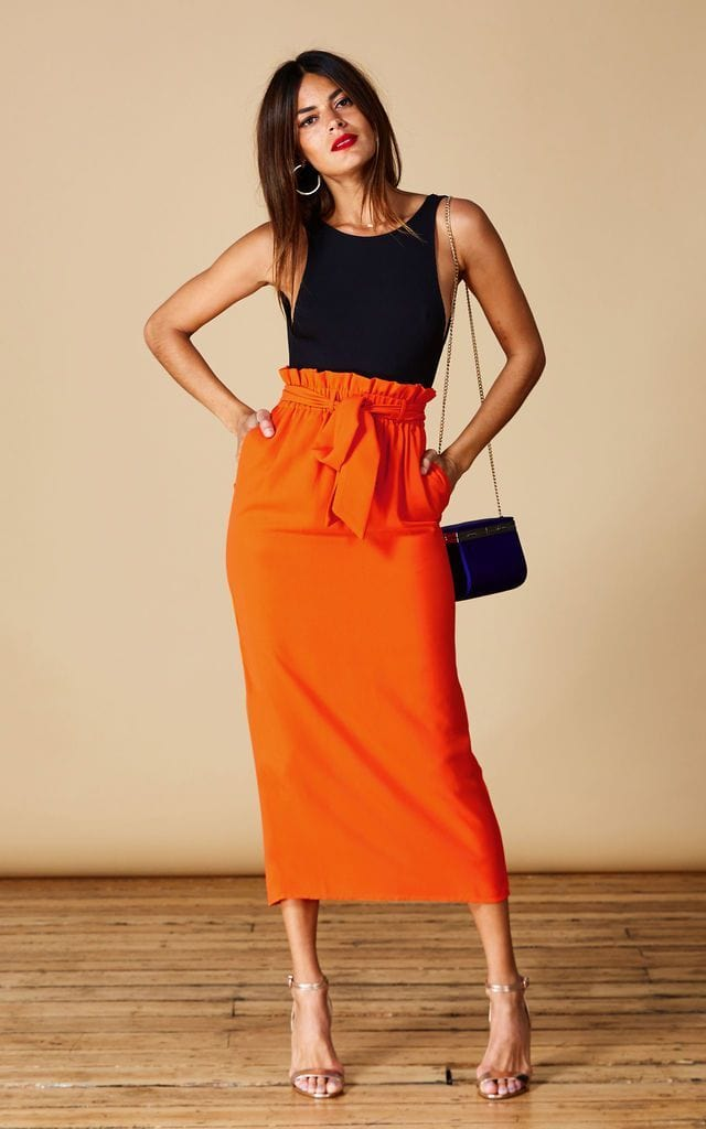 Dancing Leopard model faces forward with hands on hips wearing Willow Skirt in orange with black top