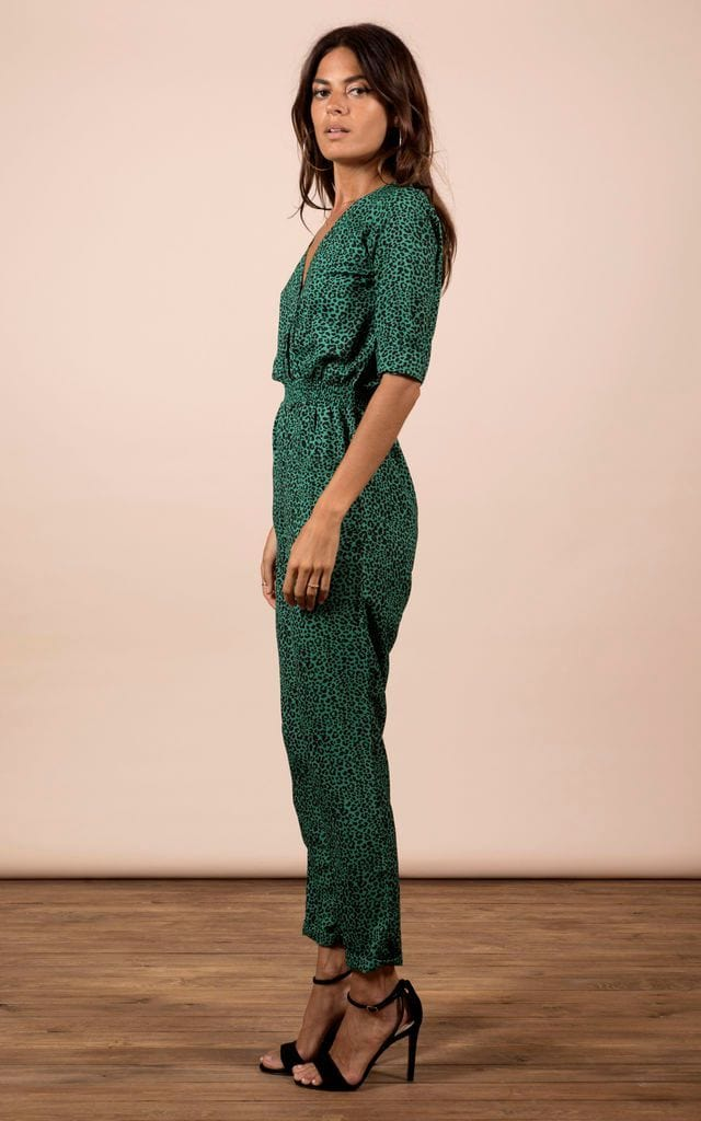 Brunette model faces sideways and looks at camera wearing Zion Jumpsuit in green leopard print