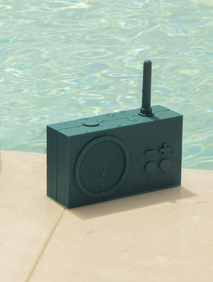 Teal, silicone, rectangular radio with minimal buttons and a short antenna, sitting poolside on a tan, stone surface, speckled with water droplets.