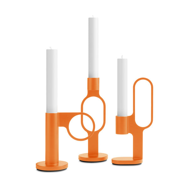 Set of three bright orange candlesticks each holding a white candle. The candlesticks are cylindrical, each offering a different circle or oval shaped handle, with a sturdy disk base.