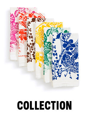 "Cascade stack of six folded napkins, each with a different vibrantly colored floral graphic printed on   white, flour-sack like fabric. Colors from left to right are: magenta, red orange, brown, yellow, green, blue. Text below the image says ""Collection"" in all caps."