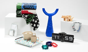 Editorial photo of vibrant holiday gift suggestions, primarily in silvers, blues, reds, and greens, on a white background.