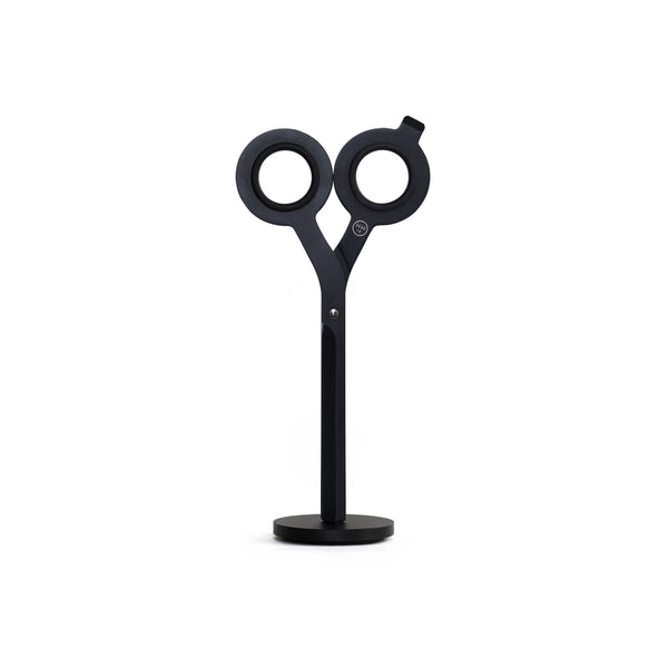 Pair of modern, geometric, black scissors standing upright in a small black disk base.