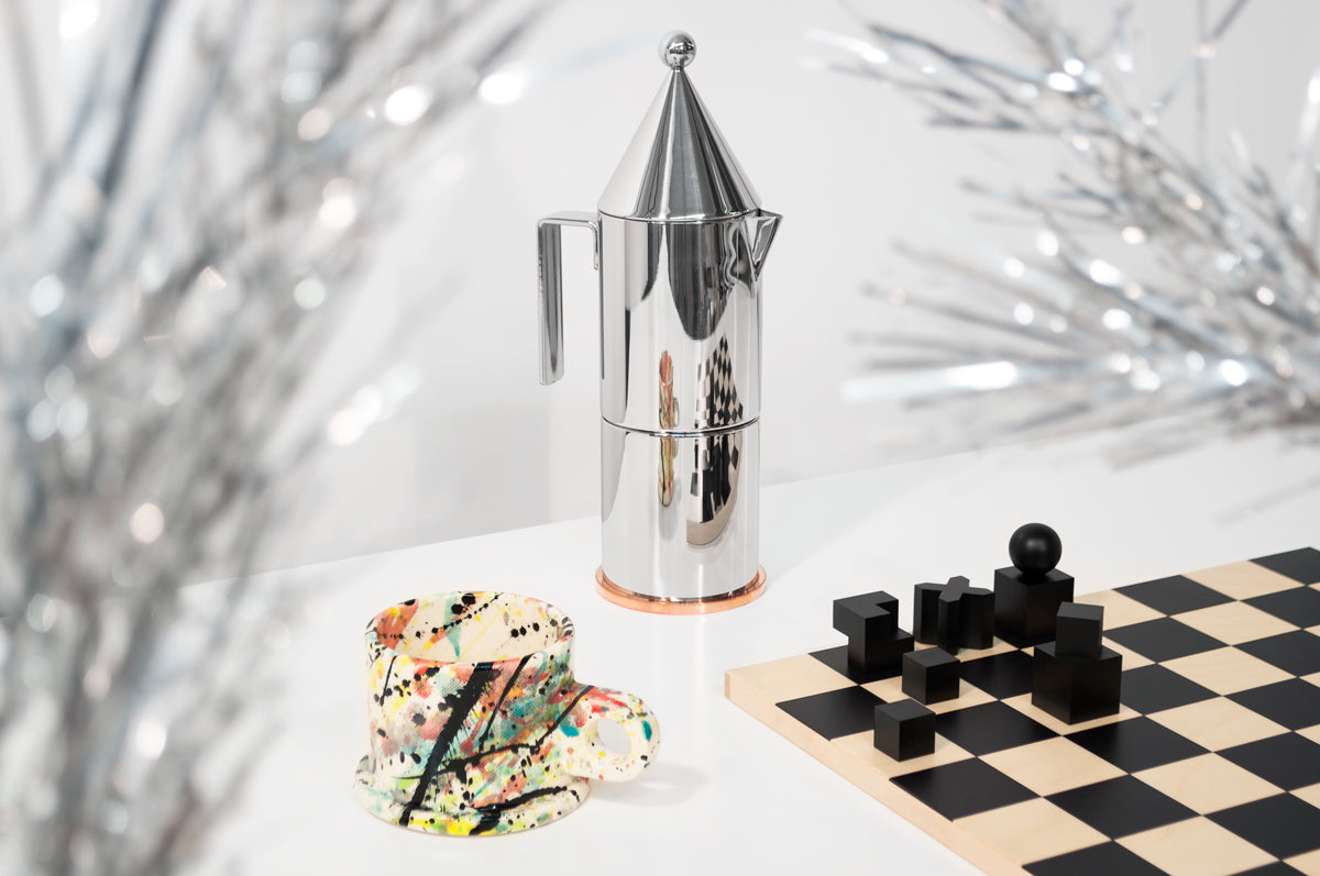 Three products on a white surface with a gray wall behind them: a tall, geometric stainless steel espresso maker at the center, a short ceramic mug covered in multicolored paint splatters at the front left, and a chessboard with black geometric pieces at the front right. Twinkly tinsel tree branches are out of focus in the foreground.