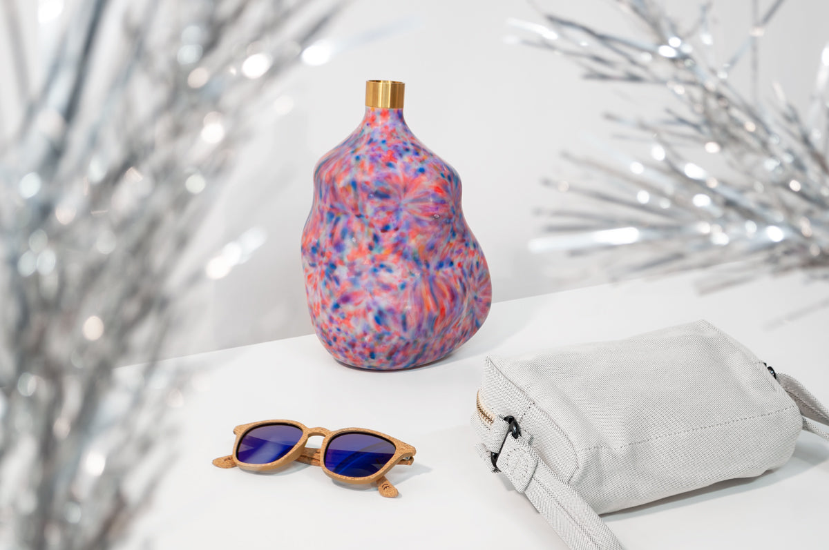 Three products on a white surface with a gray wall behind them: an irregularly shaped, multicolored vase with a brassy neck at the center, a pair of cork sunglasses with blue lenses at the front left, and a textured gray hip pouch at the front right. Twinkly tinsel tree branches are out of focus in the foreground.