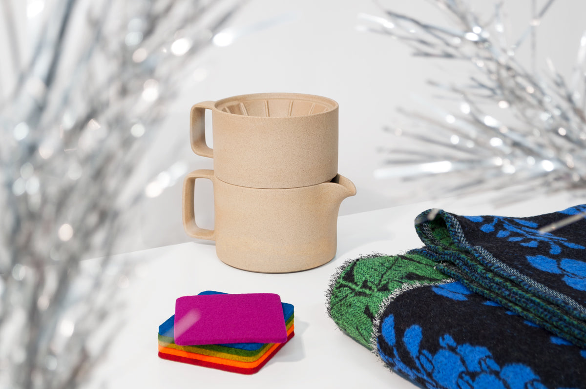 Three products on a white surface with a gray wall behind them: a sandy-colored ceramic dripper stacked on a matching kettle at the center, a rainbow stack of square, felt coasters at the front left, and folded blanket with a blue and green floral pattern on a black background at the front right. Twinkly tinsel tree branches are out of focus in the foreground.