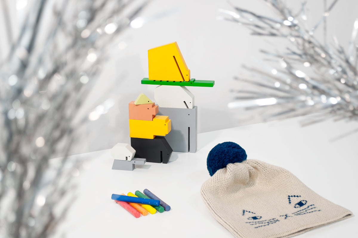 Three products on a white surface with a gray wall behind them: three stacks of minimal, colored wooden animals at the center, six brightly colored sticks of chalk in a row at the front left, and an off-white knit hat with a blue pom pom and blue cat face at the front right. Twinkly tinsel tree branches are out of focus in the foreground.