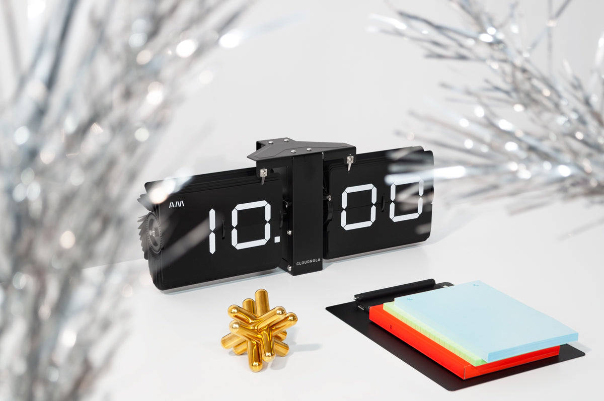 Three products on a white surface with a gray wall behind them: a long, black flip clock at the center, a jack-shaped puzzle comprised of brass bars at the front left, and a black clipboard stacked with red, green, and blue papers at the front right. Twinkly tinsel tree branches are out of focus in the foreground.