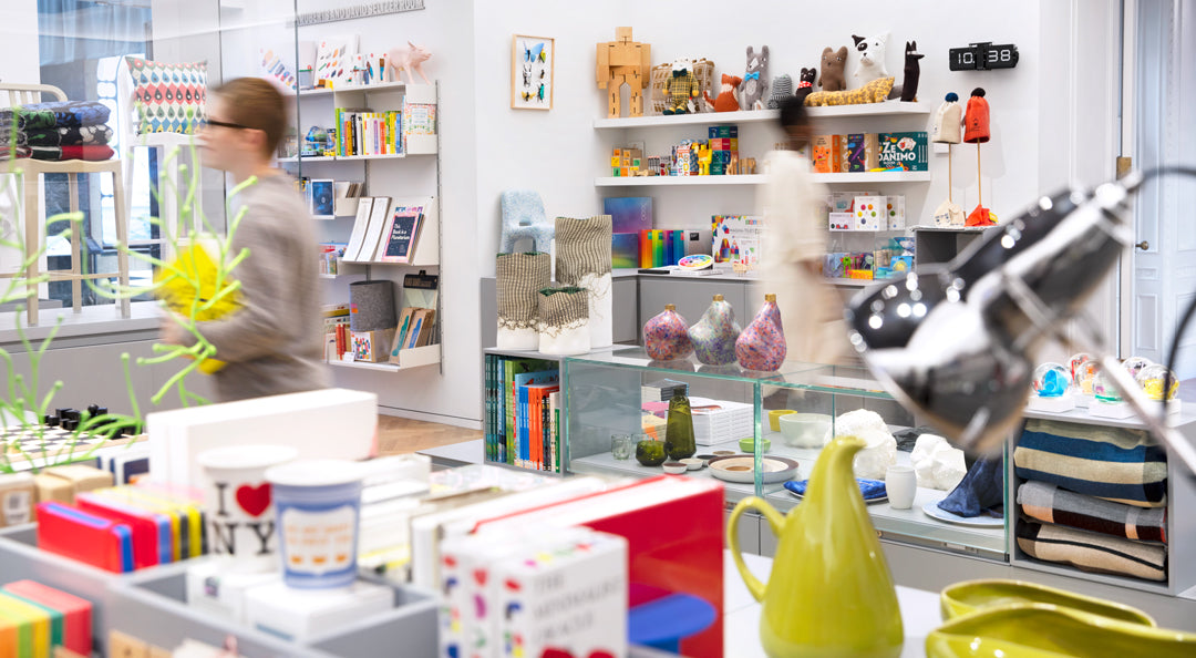 Photo of the store, a white space filled with colorful items, with two blurred people moving through it. The foreground is blurred, you can make out the shapes of books, cups, a pitcher, a reflective lamp. In the background there is a glassed in area with two chairs, a wall-mounted full bookshelf, and shelves full of toys. The sharp center of the image features several vases on top of a glass case.