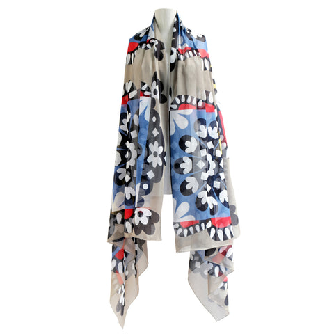 Image of a Kestler scarf draped around a mannequin bust. The scarf has a grey and light blue color blocked background. Layered over is a black and white abstract floral pattern with touches of red.