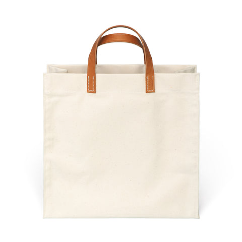 Square shaped canvas bag in natural with medium brown leather handles