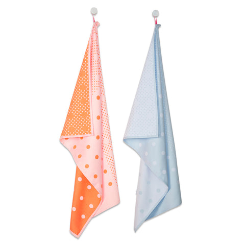 Two tea towels, one in a bright orange color and the other in a baby blue color. A large dot print is featured on each towel.