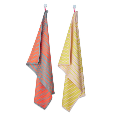 A set of two-toned tea towels decorated with micro dots. The first tea towel is a dark orange and light blue combo, the second towel is a bright yellow and soft orange combo.