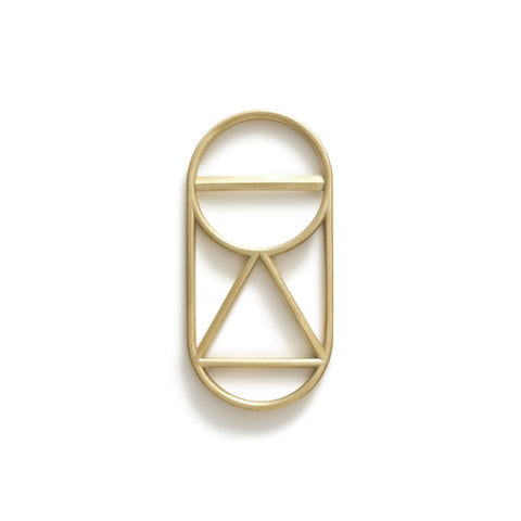 This openwork bottle opener is an elongated brass oval with triangle and circle cutouts.