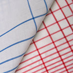 A detail of the tea towel, showing the weave, blue on the left fold, red on the right.