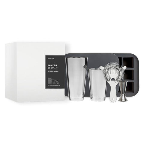 "White box with text ""Shaken Cocktails"" on a gray label, next to the two halves of a cocktail shaker, a strainer, and a jigger, all in front of a gray ice cube tray with a lid."