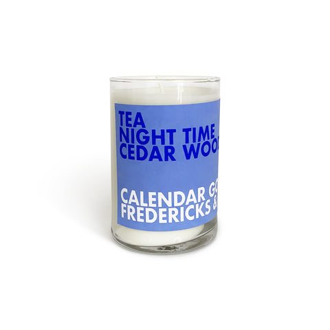 "Candle in a tall glass jar that has a light blue label on the front with bold text that says ""Tea Night Time Cedar Wood"" in blue and ""Calendar Goods"" ""Fredericks & Mae"" in white underneath."