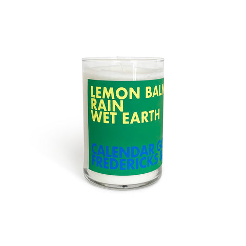 "Candle in a tall glass jar that has a green label on the front with bold text that says ""Lemon Balm Rain Wet Earth"" in yellow and ""Calendar Goods"" ""Fredericks & Mae"" in blue underneath."