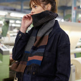A young female model with medium brown hair poses in profile in an out-of-focus interior factory setting, wearing a dark, long-sleeved blue denim jacket and Dark Glebe Wool Scarf around her neck, pulled up over her mouth.
