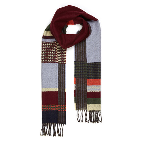 Red Glebe Wool Scarf shown on a white background, double-sided, with a pattern of defined aysmetical stripes and zig-zag twills in maroon, orange, lavender, gray, navy, green and pale yellow, with dark gray fringe.