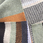 Close-up view of four quadrants of a folded Sage Glebe Wool  Scarf fills the frame, showing signature aysmetical stripes, blocks of color, and zig-zagging twills.
