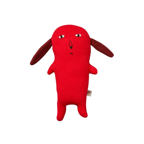 Front view of the childish Rusty Plush. Rusty is a miscellaneous creature who kind of looks like a dog. It has a flat red body and roud head with no neck, standing on two legs with little arms stuck out of the sides. It has long, thin dark red ears, bulbous almond-shaped eyes, with a stitched on almond-shaped nose and short, line mouth in a pleasant, neutral expression.