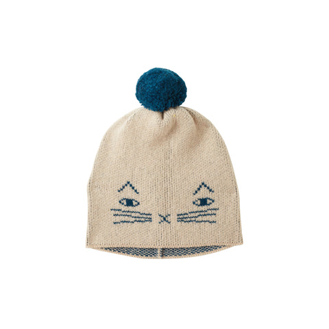 Knitted hat in Oatmeal with a blue pompom on top and blue outlines of a cat's features including whiskers, arched ears, oval eyes and an x-shaped mouth and nose.
