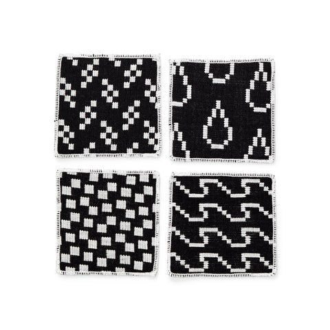 An overhead photograph of a black and white coaster set laid out in a grid to show the four different geometric patterns.