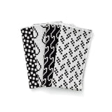 A set of black and white napkins fanned out to show the four different geometric patterns.