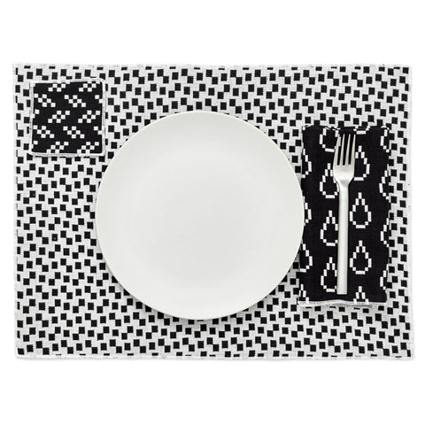 Overhead view of a place setting including a placemat, napkin and coaster with a mix of black and white Bitmap patterns.