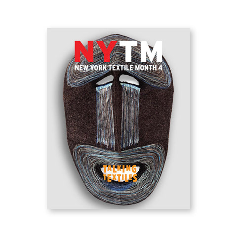 Gray magazine cover with a multi media and multi textural mask with magazine title in orange centered over the mouth opening and the magazine logo in red and white near the top