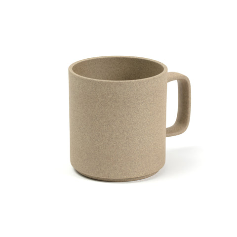 3/4 view of a mug on a white background. The color and texture is like pressed sand. Mug has straight sides and a rectangular handle that has rounded corners.