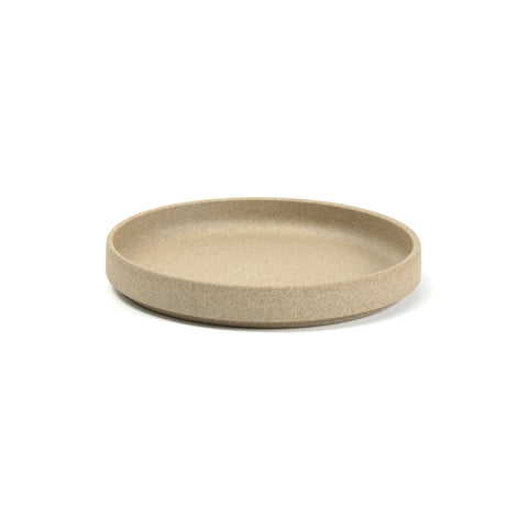 A round, minimalist plate on a white background, the color and texture of pressed sand. Plate has a flat bottom and straight sides with a slight indentation near the base.