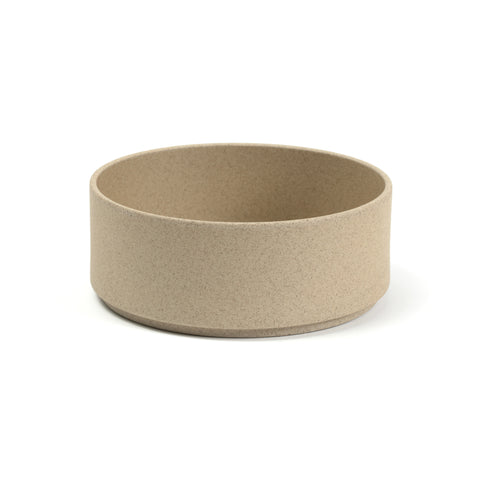 A round, minimalist soup bowl with a flat bottom and straight sides slightly indented near the base.The color and texture are like pressed sand.