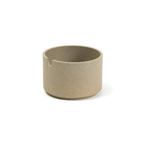 A cylindrical sugar vessel, the color and texture of pressed sand, on a white background. The vessel has straight sides with a slight indentation near the bottom, and has a u shaped cut out near the top for use as a spoon rest.