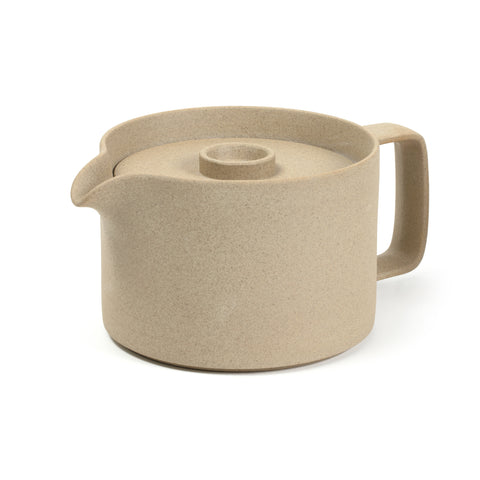 3/4 view of a tea pot on a white background. The color and texture is like pressed sand. Tea pot has straight sides and a rectangular handle that has rounded corners. It has a small spout that curves down from the top edge. A flat, round lid fits inside the top edge, with a handle that circle that protrudes straight up from the center of the lid and is concave.