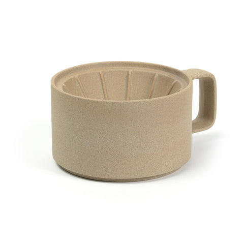 3/4 view of a coffee dripper on a white background. The color and texture is like pressed sand. Dripper has straight sides and a rectangular handle that has rounded corners. The inside of the dripper is a funnel with ridges.
